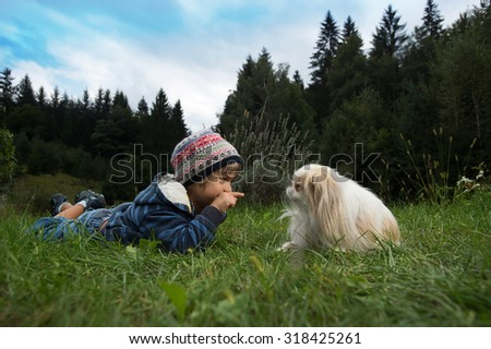Cute little boy and his dog rolling on the grass looking at each other - stock photo
