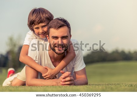 Cute little boy and his handsome young dad are looking at camera and smiling while lying on the grass in the park. Son is pickaback - stock photo