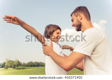 Cute little boy and his handsome young dad are looking at each other and smiling while playing in the park - stock photo