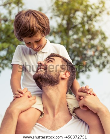 Cute little boy and his handsome young dad are looking at each other and smiling while resting in the park. Son is sitting on his father's shoulders - stock photo