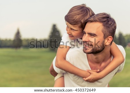 Cute little boy and his handsome young dad are looking forward and smiling while resting in the park. Son is sitting pickaback - stock photo