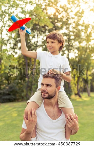 Cute little boy and his handsome young dad are smiling while playing with a toy airplane in the park. Son is sitting on his father's shoulders - stock photo