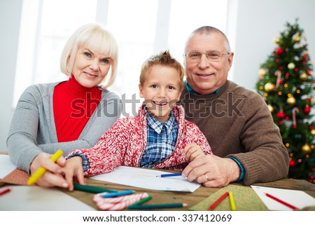 Cute little boy and his happy grandparents looking at camera - stock photo