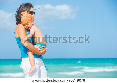 Cute little boy and his mother at beach in the background of the sea - stock photo