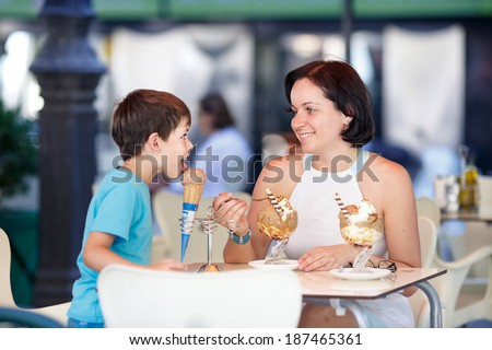 Cute little boy and his mother eating ice-cream in an outdoor cafe - stock photo