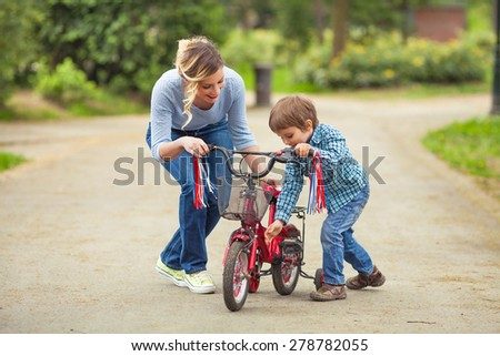 Cute little boy and his mother playing with bicycle in a park - stock photo