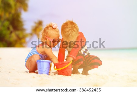 cute little boy and toddler girl play on beach - stock photo