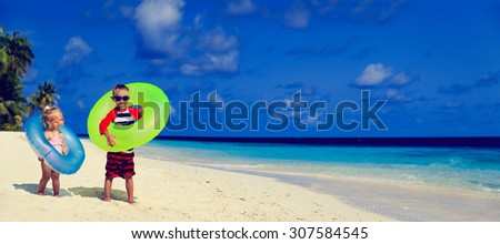 cute little boy and toddler girl play on tropical beach, wide panorama ideal for banners - stock photo