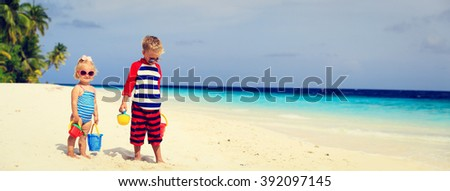 cute little boy and toddler girl play with sand on beach - stock photo