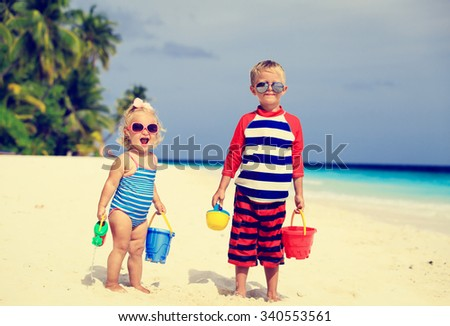 cute little boy and toddler girl play with sand on tropical beach - stock photo