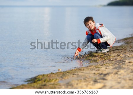 Cute little boy at sand beach on autumn day - stock photo