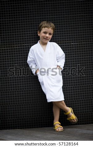 Cute little boy at spa wearing bathrobe