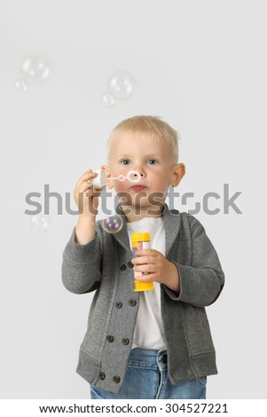 Cute little boy blow bubbles on gray background - stock photo
