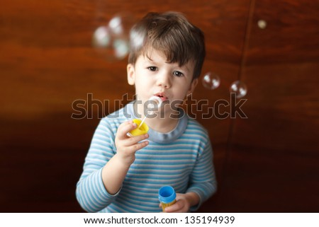 Cute little boy blowing bubbles at home - stock photo