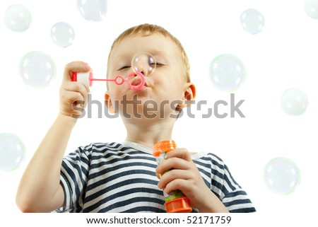 cute little boy blowing bubbles on white background - stock photo