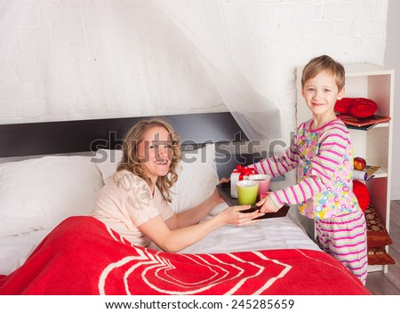 Cute little boy brings tray with breakfast and present to his mom laying in bed