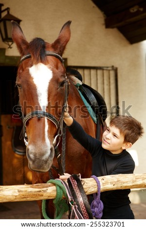 Cute little boy caressing horse. - stock photo