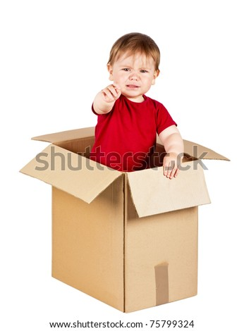 Cute little boy crying in a big carton box. Isolated on white.