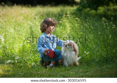 Cute little boy cuddling his dog in nature - stock photo