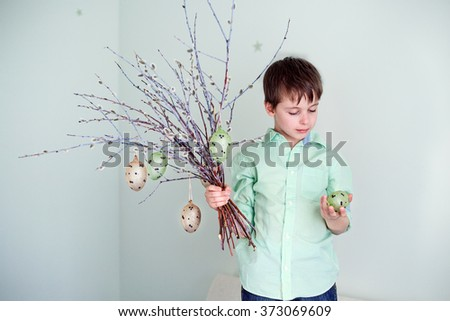 Cute little boy decorating pussy willow twigs with hanging easter eggs indoors - stock photo