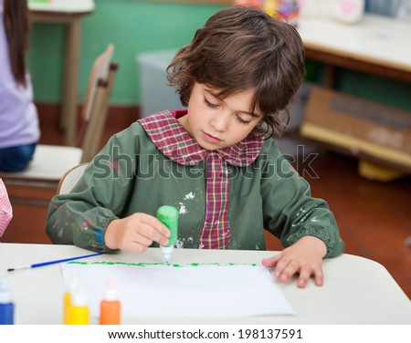 Cute little boy drawing at desk in art class - stock photo