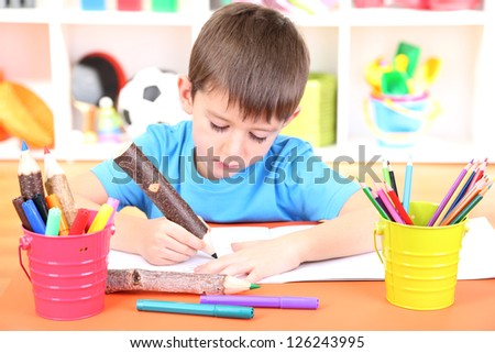 Cute little boy drawing in his album