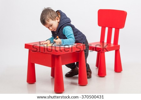Cute little boy drawing, red table and chair, on white background. Childhood education concept - stock photo