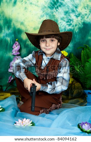 cute little boy dressed as a cowboy with a gun on a green background