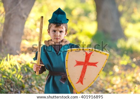 Cute little boy dressed as a knight playing with a sword and a shield in the forest - stock photo