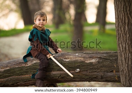 Cute little boy dressed up as a knight playing in the woods with a handmade sword