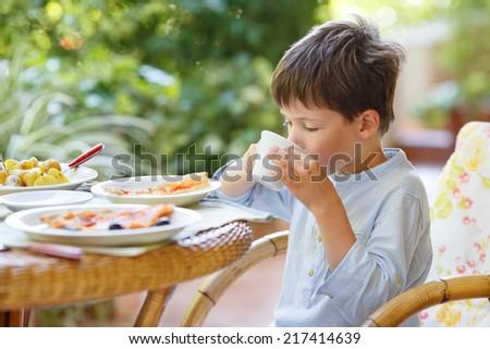 Cute little boy drinking hot chocolate - stock photo