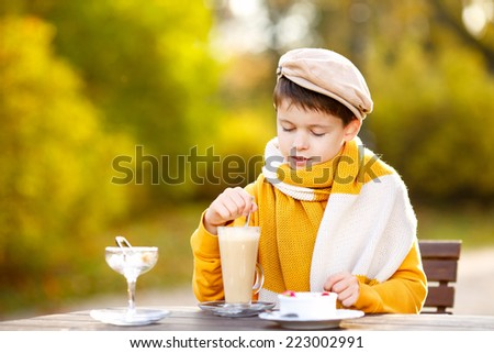 Cute little boy drinking hot chocolate in cafe on beautiful autumn day - stock photo