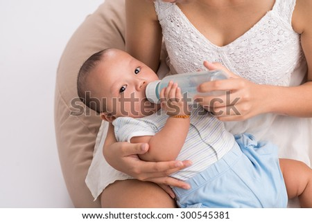 Cute little boy drinking milk from the bottle and looking at the camera