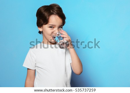 Cute little boy drinking water from glass on blue background