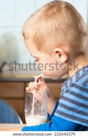Cute little boy drinks milk using a drinking straw - stock photo