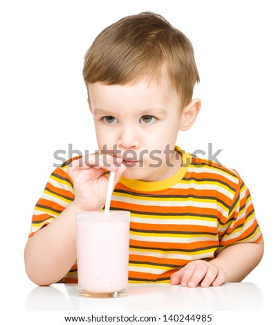 Cute little boy drinks milk using a drinking straw, isolated over white - stock photo