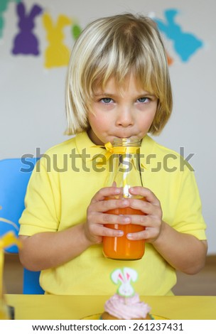Cute little boy drinks orange juice using drinking straw - stock photo