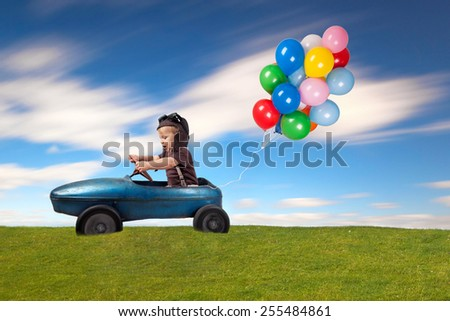 cute little boy driving vintage old toy car with colorful balloons and having fun - stock photo