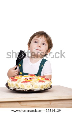Cute little boy eating a cake. Isolated on white.