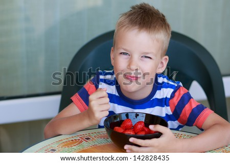 Cute little boy eating a strawberry - stock photo