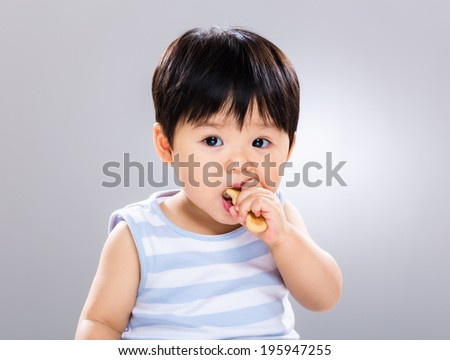 Cute little boy eating cookie - stock photo