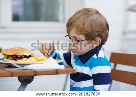 Cute little boy eating fast food: french fries and hamburger in cafe - stock photo