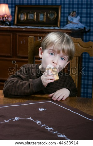 Cute little boy eating ice cream at the table - stock photo