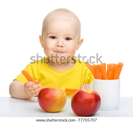 Cute little boy eats carrot and apples, isolated over white - stock photo