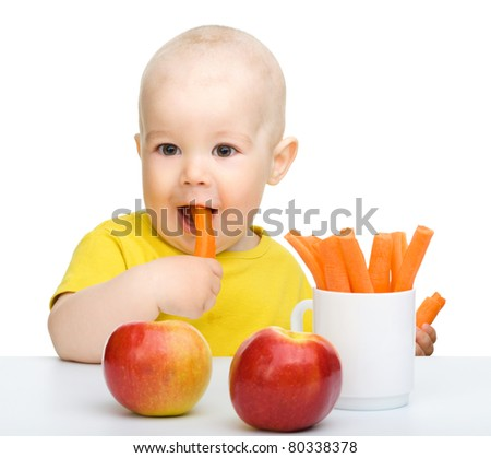 Cute little boy eats carrot and apples, isolated over white