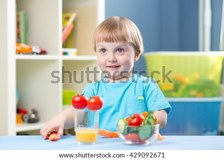 Cute little boy eats carrot and other vegetables in room