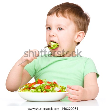 Cute little boy eats vegetable salad using fork, isolated over white - stock photo