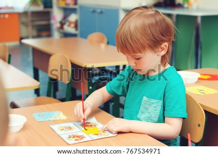 Cute little boy engaged in art and craft in a classroom . Learning and education concept.
