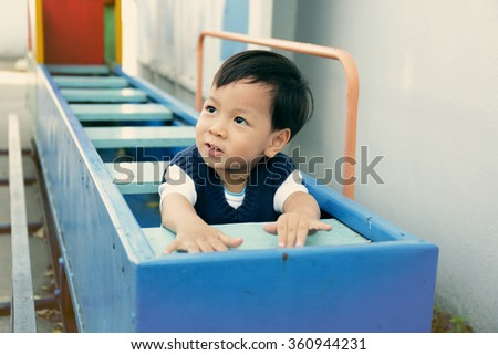 Cute little boy enjoy playing at the playground (colorized effect) - stock photo
