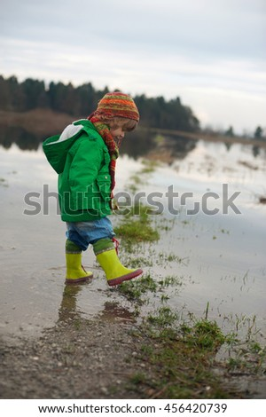Cute little boy enjoys playing in muddy puddles. Happiness in gloomy weather.